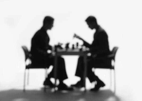 Men strategically playing chess